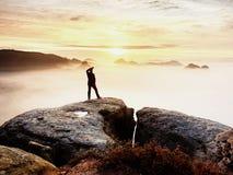 Estada da silhueta do homem no pico afiado da rocha Satisfaça o caminhante apreciam a vista Homem alto no penhasco rochoso foto de stock royalty free