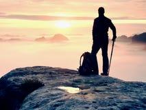 Estada da silhueta do homem no pico afiado da rocha Satisfaça o caminhante apreciam a vista Homem alto no penhasco rochoso Fotografia de Stock