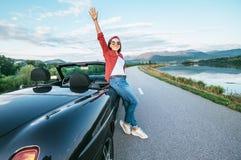 Estada de sorriso feliz da jovem mulher perto do carro do cabriolet no MOU imagens de stock royalty free