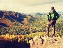 Estada do homem no pico afiado da rocha Satisfaça o caminhante apreciam a vista Homem alto no penhasco rochoso que olha para baix imagem de stock royalty free