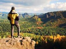 Estada do homem no pico afiado da rocha Satisfaça o caminhante apreciam a vista Homem alto no penhasco rochoso que olha para baix fotografia de stock royalty free
