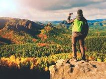 Estada do homem no pico afiado da rocha Satisfaça o caminhante apreciam a vista Homem alto no penhasco rochoso que olha para baix imagens de stock royalty free