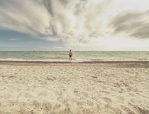 Estada do menino do cabelo louro na maré fria do mar Criança na praia rochoso com ondas espumosas Dia ventoso imagem de stock
