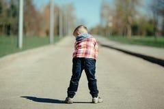 Estada do rapaz pequeno para trás na rua Fotografia de Stock Royalty Free