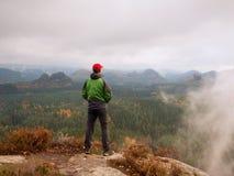 Estada do turista do homem no pico afiado da rocha O caminhante sozinho no tampão vermelho e o revestimento verde apreciam a vist imagens de stock royalty free