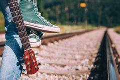 Estada do viajante do homem na estrada de ferro - sapatilhas e close up da guitarra mim fotos de stock royalty free