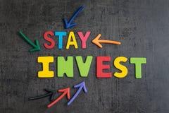A estada investida no estoque sem o conceito do sincronismo do mercado, setas que apontam às palavras ESTADA INVESTE na parede do imagens de stock