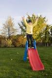 Estada positiva da criança na corrediça com grama verde AR Fotografia de Stock Royalty Free