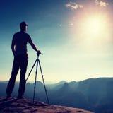 Estada profissional do fotógrafo com o tripé no penhasco e no pensamento Paisagem sonhadora do fogy, nascer do sol enevoado azul  fotografia de stock