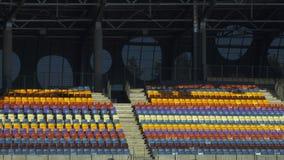 Estadio de fútbol con nadie de tribunas Diversos asientos vacíos de los colores almacen de video