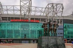 Estadio de fútbol del Manchester United con la estatua del mejor, de la ley y de Charlton en el primero plano foto de archivo libre de regalías