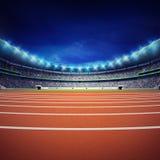 Estadio del atletismo con la pista en la opinión delantera general de la noche Fotografía de archivo