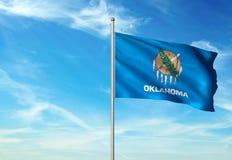 Estado de Oklahoma de la bandera de Estados Unidos que agita el ejemplo realista 3d del fondo del cielo azul imagenes de archivo
