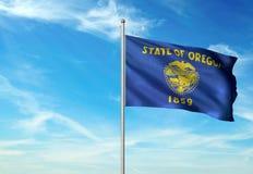 Estado de Oregon de la bandera de Estados Unidos que agita el ejemplo realista 3d del fondo del cielo azul imagen de archivo