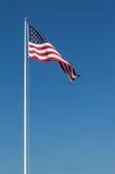 Estados Unidos grandes señalan por medio de una bandera y cielo azul Imagenes de archivo