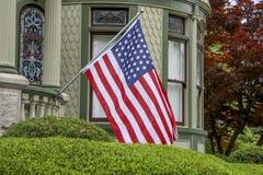 Estados Unidos señalan por medio de una bandera en casa victoriana Fotos de archivo libres de regalías