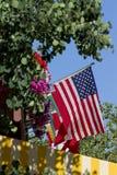 Estados Unidos señalan por medio de una bandera rodeado por los árboles de las flores y el cielo azul Imagenes de archivo