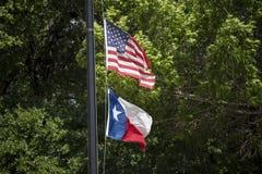 Estados Unidos señalan por medio de una bandera y bandera de Tejas en el viento del verano fotos de archivo