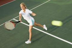 Estafa de balanceo del jugador de tenis en el movimiento del cuarto delantero Imagenes de archivo