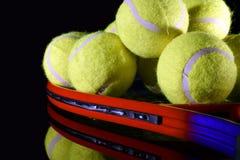 Estafa de tenis y pila de pelotas de tenis Fotografía de archivo