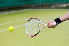 Estafa y bola de tenis en la acción Fotografía de archivo