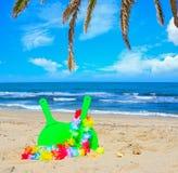Estafas de la playa bajo ramas de la palma Imagen de archivo libre de regalías