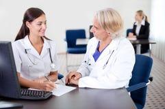 Estagiário novo que senta-se com um doutor maduro fotografia de stock