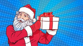 Estallido Art Comic Background Merry Christmas de Santa Claus Hold Gift Box Over y diseño del cartel de la Feliz Año Nuevo Foto de archivo libre de regalías