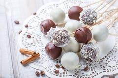 Estallidos de la torta adornados con el chocolate y el coco blancos, oscuros en la servilleta, luz natural Imagenes de archivo