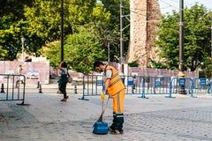 Estambul, el 15 de junio de 2017: portero en el uniforme brillante de la naranja que barre la teja en la calle en el distrito de  Imagenes de archivo