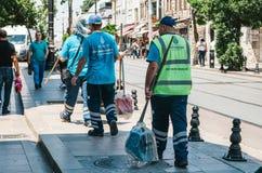 Estambul, el 15 de junio de 2017: Tres porteros de la calle en uniformes están caminando abajo de la calle que sostiene las escob Fotos de archivo