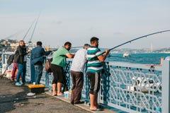 Estambul, el 15 de junio de 2017: Muchos pescadores de la población local se colocan en el puente y los pescados de Galata El tra Fotos de archivo