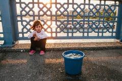 Estambul, el 15 de junio de 2017: Niña linda que se sienta delante de un cubo de pescados en el puente de Galata Foto de archivo