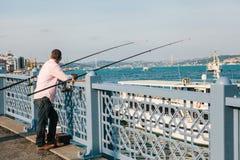 Estambul, el 15 de junio de 2017: Un pescador de la población local se coloca en el puente y los pescados de Galata Afición tradi Fotos de archivo