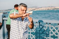 Estambul, el 15 de junio de 2017: Un pescador de la población local se coloca en el puente y los pescados de Galata Afición tradi Foto de archivo libre de regalías