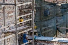 Estambul, Turquía, el 22 de septiembre de 2018: Trabajadores de construcción en un andamio durante trabajo de la reparación y de  fotos de archivo libres de regalías