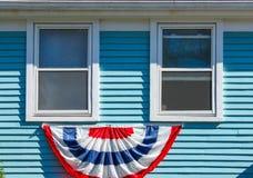 Estamenha patriótica indicada abaixo de duas janelas de madeira em uma casa azul do painte para Memorial Day ou 4o julho EUA Imagens de Stock