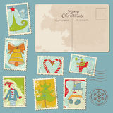 Estampilles et carte postale de Noël de cru Photographie stock