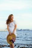 Estancia blanca del vestido de la chica joven que lleva en el coste del mar Imagen de archivo libre de regalías