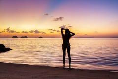 Estancia de la chica joven en la playa y la observación de la puesta del sol Foto de archivo