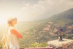 Estancia de la mujer joven en el borde del acantilado que mira sobre la vista expansiva de llanos y de montañas fotografía de archivo libre de regalías