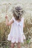 Estancia de la niña con la guirnalda del trigo en su cabeza y sostener un ramo de trigo imágenes de archivo libres de regalías