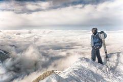Estancia del esquiador con los esquís en roca grande en el contexto de las montañas Bansko, Bulgaria foto de archivo libre de regalías