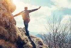 Estancia del hombre del escalador al borde de profundamente con la opinión sobre la montaña v imagenes de archivo
