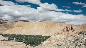 Estancia del viajero de dos ciclistas en el top de la montaña Fotografía de archivo