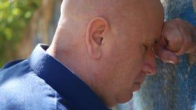 Estancia enojada del hombre con la cabeza en la pared que piensa en problemas metrajes