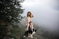 Estancia fresca del border collie de la muchacha y del perro en el borde de la roca en mirada de la niebla adelante en mirada del imagenes de archivo