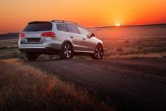 Estancia gris del coche en el camino de tierra en la puesta del sol Foto de archivo
