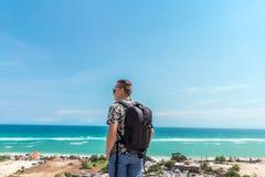 Estancia hermosa del hombre del viajero por el fondo azul del océano - individuo feliz que se relaja en el punto de opinión del m foto de archivo libre de regalías