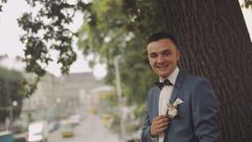 Estancia hermosa del novio cerca del árbol en la calle de la ciudad Día de boda Cámara lenta Pocos tiros almacen de video